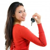 Attractive young woman holding her first own car key isolated on white background. Beautiful mixed r