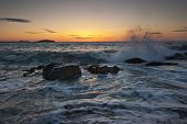 image of marblehead  - Waves crash and shoot into the air on a rocky beach at sunrise - JPG
