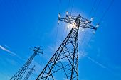 stock photo of power transmission lines  - a power mast of a high voltage transmission line against blue sky with sun - JPG