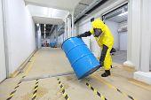 picture of bio-hazard  - technician in uniform rolling barrel with hazardous substance - JPG
