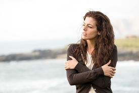 picture of heartbreaking  - Sad shivery woman in brown sweater jacket hugging herself on late summer cold day in coast landscape - JPG