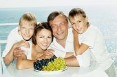 Happy family with a plate of grapes