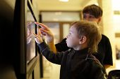 stock photo of realism  - Mother with her son using touch screen in a museum - JPG