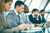stock photo of seminar  - Row of business people listening to presentation at seminar with focus on elegant young man - JPG
