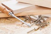 stock photo of joinery  - Close up view of a Phillips head screwdriver and threaded metal wood screws with one screw inserted into a plank of wood in a carpentry joinery and construction concept - JPG