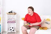 foto of couch potato  - Lazy overweight male sitting with fast food on couch and watching television - JPG