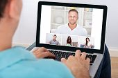 foto of video chat  - Man having video conference with friends on laptop at home - JPG