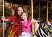 picture of carnival ride  -  a young mother and her daughter riding on a merry go round at t - JPG