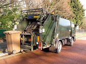 stock photo of waste management  - Garbage truck with elevated wheelie bin in use - JPG