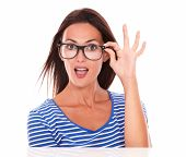 stock photo of spectacles  - Happy female holding spectacles while smiling and looking at you front view in white background - JPG