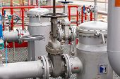 stock photo of refinery  - detail of oil pipeline with valves in large oil refinery - JPG