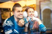 stock photo of iroquois  - Young loving couple dressed in blue sweater sitting with knitted coffee cups at the cafe in winter - JPG