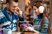 stock photo of iroquois  - Man making proposal giving a gift box to his girlfriend dressed in blue sweaters in the cafe - JPG