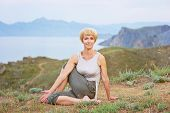 image of discipline  - Senior woman doing yoga exercises with mountain on the background