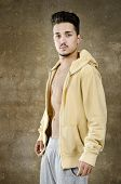 picture of machete  - Latin man posing on dirty wall background with open sportswear jacket - JPG