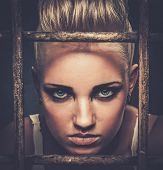 picture of delinquency  - Troubled teenager girl behind bars - JPG