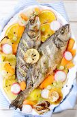 picture of bass fish  - Prepared bass fish in the plate ith vegetables and fruit - JPG