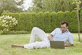 picture of recliner  - Full length of young man using laptop while reclining in park - JPG