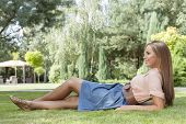 foto of recliner  - Full length of happy young woman reclining on grass in park - JPG