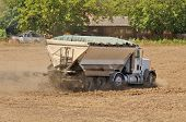 image of spreader  - Agricultural fetilizer spreader working a newly plowed field in preperation for a new vineyard - JPG