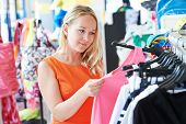 picture of apparel  - woman choosing dress during shopping at garments apparel clothing shop - JPG