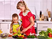 foto of pinafore  - Children little girl cooking on their own at kitchen - JPG