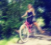 stock photo of bike path  - a girl riding a bike on a path in a park full of trees toned with a retro vintage instagram filter and a motion blur  - JPG