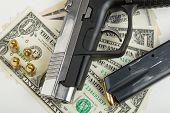 image of corruption  - detail of gun with bullet on US dollar banknotes crime or corruption concept - JPG