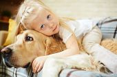 stock photo of lie  - Cute child lying on fluffy pet - JPG