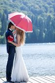 foto of dock a lake  - Married couple standing on a footbridge at the lake kissing under a pink umbrella - JPG
