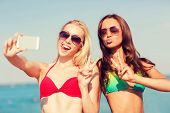 image of two women taking cell phone  - summer vacation - JPG