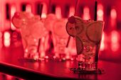 foto of collins  - Four Tom Collins cocktails shot on a bar in night club in dim light - JPG