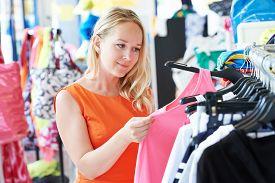 stock photo of apparel  - woman choosing dress during shopping at garments apparel clothing shop - JPG