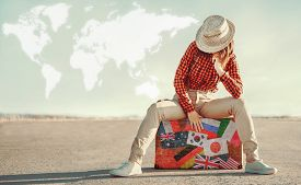 picture of flags world  - Traveler woman sits on suitcase with stamps flags of different countries - JPG
