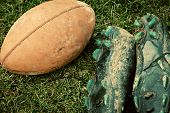 close up of an american football and sports shoes covered with mud poster