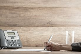 picture of politician  - Closeup of female lawyer or executive signing a contract placed on desk near the telephone with copy space on wooden wall - JPG