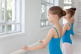 stock photo of ballet barre  - Three little ballet girls posing at ballet barre together on white studio background - JPG