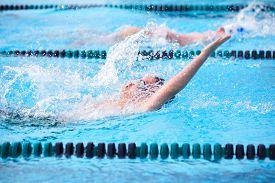 picture of swim meet  - Motion blur image of a boy swimming backstroke in a race - JPG