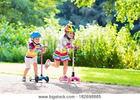 Kids Riding Scooter In Summer