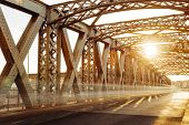 Asphalt Road Under The Steel Construction Of A City Bridge On A Sunny Day. Urban Scene In The Bridge poster