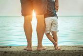 Father and son stay on the sea beach under sunlight at summer time. Close-up foots view on the seali poster