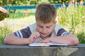 stock photo of school child  - The little boy writes to the writing - JPG
