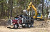 stock photo of dumper  - Excavator loading dumper truck with dirt at construction site - JPG