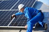 Male Worker In Blue Suit And Protective Helmet Installing Solar Photovoltaic Panel System Using Scre poster