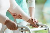 Closeup Of Senior Ladys Hands Holding A Walker And Helpful Nurse Supporting Her poster