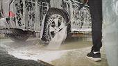Man Worker Washing Cars Alloy Wheels On A Car Wash. Car Wash Wash The Car At The Car Wash. poster