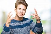 Young handsome man over isolated background Shouting frustrated with rage, hands trying to strangle, poster