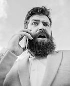 Man Bearded Surprised Businessman Hold Mobile Phone Sky Background. Hipster Smartphone Call Partner. poster