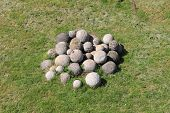 pic of cannonball  - Antique white stone cannonballs on a grass meadow - JPG