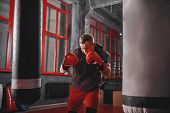 Impossible Is Nothing. Muscular Sportsman In Sport Clothing Exercising On Heavy Punch Bag Before Fig poster